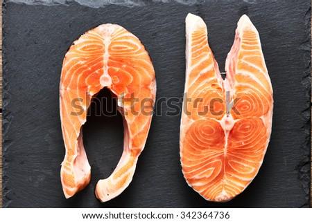 Raw salmon steaks on slate background   - stock photo