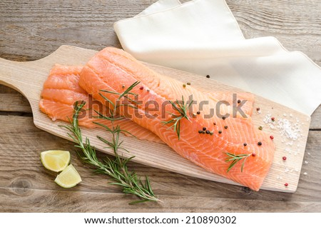 Raw salmon steaks on the wooden board - stock photo