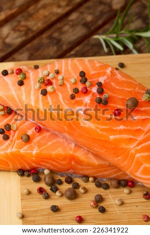 raw salmon steaks on wooden table with spices  close up