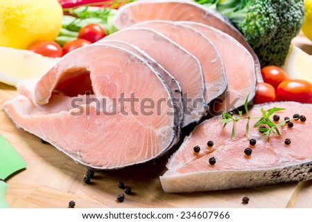 raw salmon with vegetables on cutting board