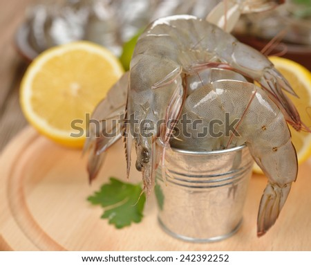 Raw shrimp with lemon on a brown background, close-up