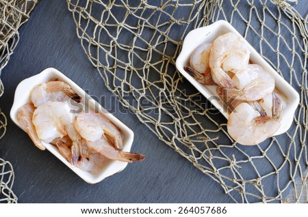 Raw shrimps on black stone with net as texture or background - stock photo