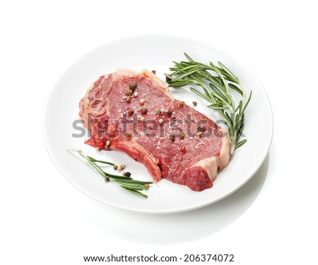 Raw sirloin steak with rosemary and spices on plate. Isolated on white background - stock photo