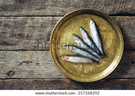 Raw smelt fishes on wooden background with blank space  - stock photo