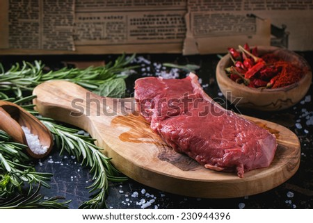 Raw steak on olive cutting board with rosemary herbs and red hot pepper over black wooden table. See series - stock photo