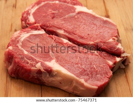 Raw Steak - raw rib eye steaks on the cutting board - stock photo