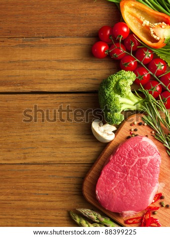Raw Steak with green asparagus and vegetables on wooden board