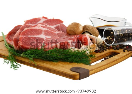 Raw steak with portobello mushrooms, pepper and soy sauce on cutting board isolated on white background - stock photo