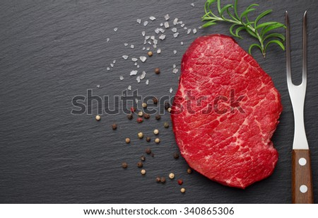 raw steak with salt and pepper on slate plate - stock photo