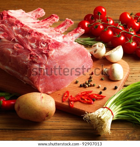 Raw Steak with vegetables on wooden board - stock photo