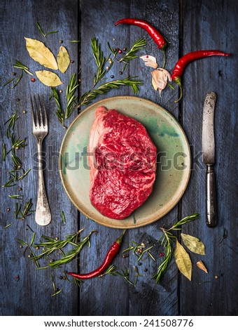 Raw Striploin Steak on  plate with  knife and fork to lay with herbs and spices, blue wooden background, top view - stock photo