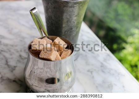 Raw Sugar Cube in Silver bow  - stock photo