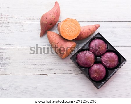 Raw sweet potatoes with potato pie on wooden white background - stock photo