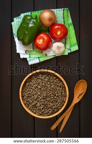Raw textured vegetable or soy protein, called also soy meat in wooden bowl with raw vegetables on kitchen towel. Photographed overhead on dark wood with natural light.  - stock photo