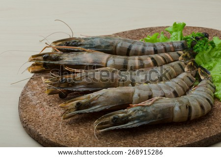 Raw tiger shrimps on the wood board - stock photo