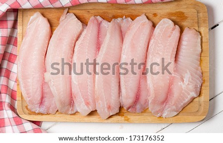 Raw tilapia fillet on a wooden board - stock photo