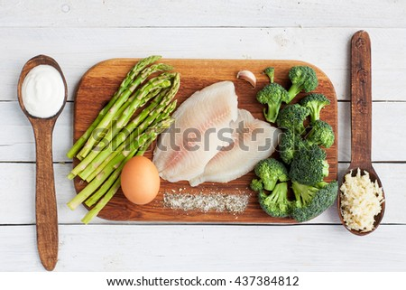 Raw tilapia fish, egg, asparagus, broccoli, cream, garlic, salt on wooden table. Fish dish preparation. Selective focus, top view - stock photo