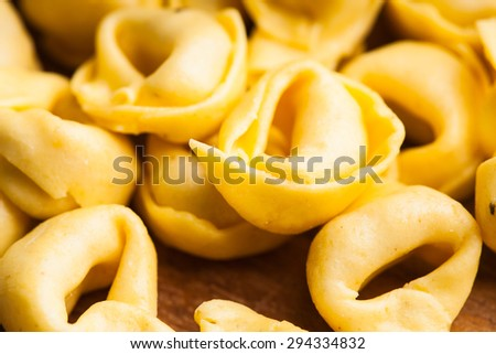 Raw Tortellini on the wooden board, prepared for cooking - stock photo