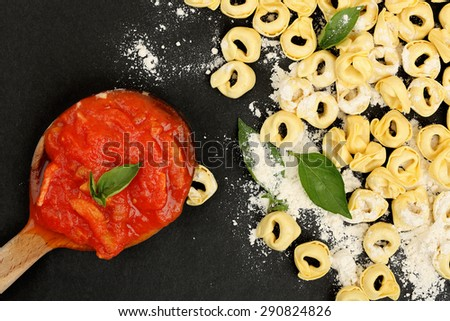 raw tortellini pasta and ladle with sauce on black surface - stock photo