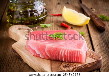 Raw tuna fillet with dill, lemon and olive oil on rustic background - stock photo