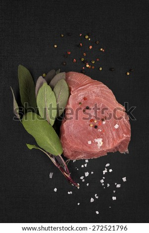 Raw tuna steak with fresh herbs isolated on black background, top view. Sashimi sushi, seafood eating, healthy food. - stock photo