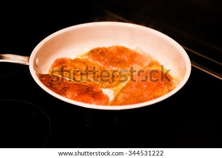 Raw turkey breast steaks seasoned with spices on a pan