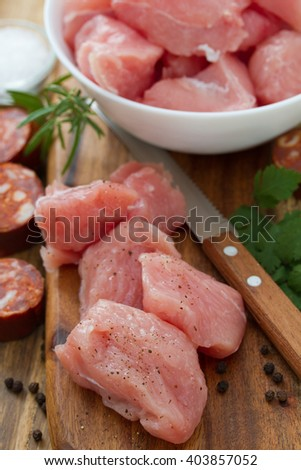 raw turkey owith black pepper on brown wooden board and chorizo - stock photo