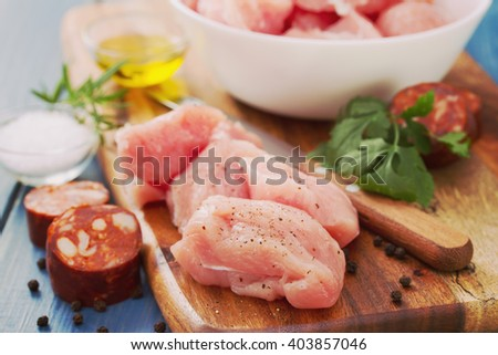raw turkey with black pepper on brown wooden board and chourico - stock photo