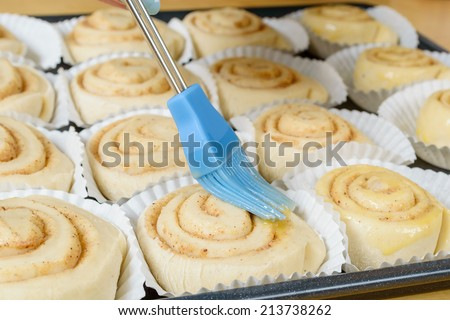 Raw, unbaked cinnamon buns brushed with beaten eggs before baking. - stock photo