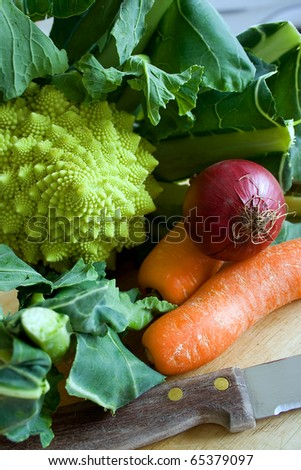 Raw uncooked Romanesco broccoli, carrots and onion on a chopping board - stock photo