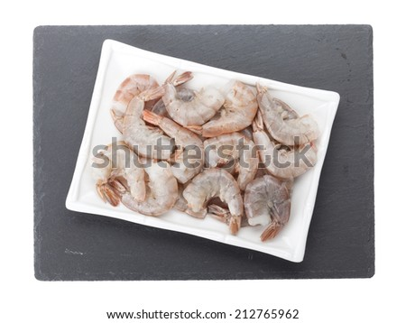 Raw uncooked shrimps plate over stone board. Isolated on white background - stock photo