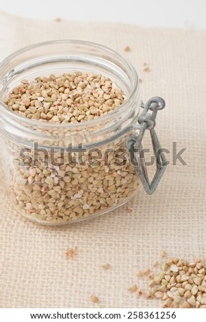 raw unroasted buckwheat groats in a glass jar - stock photo