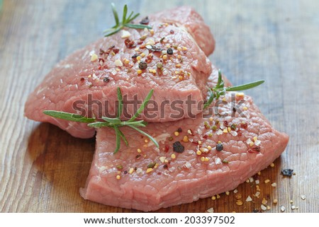 Raw veal meat steak on wooden table - stock photo
