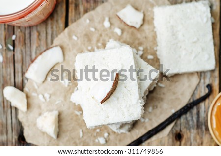 raw vegan coconut bars on a dark wood background. the toning. selective focus - stock photo