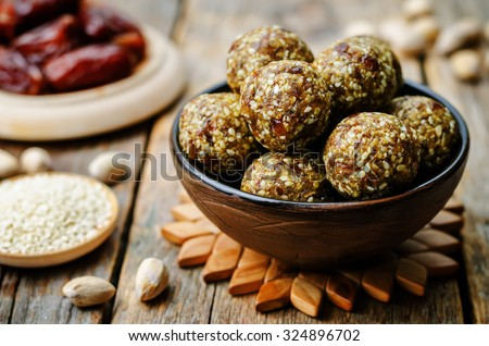 raw vegan dates sesame pistachio balls. toning. selective focus - stock photo