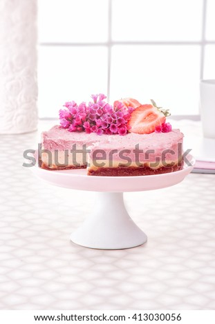 Raw vegan strawberry or raspberry cheesecake gluten-free on a white decorate table and window background, Raw Vegan Paleo Diet Cheesecake Gluten-Free with Dates and Cashews,  Horizontal - stock photo