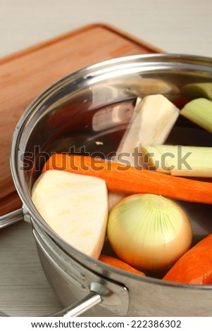 Raw Vegetables add into saucepan. Making vegetables bouillon. - stock photo