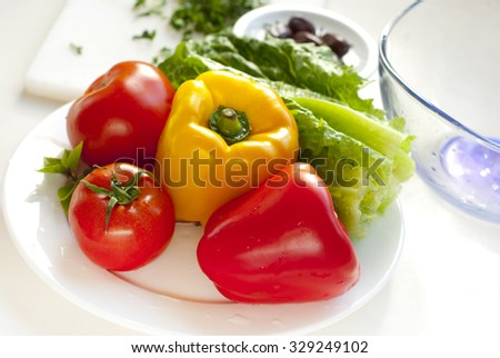 raw vegetables for salad on white plate