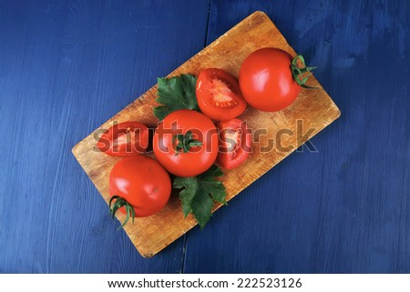 raw vegetables : some uncooked ripe fresh tomatoes over blue table on cutting board - stock photo