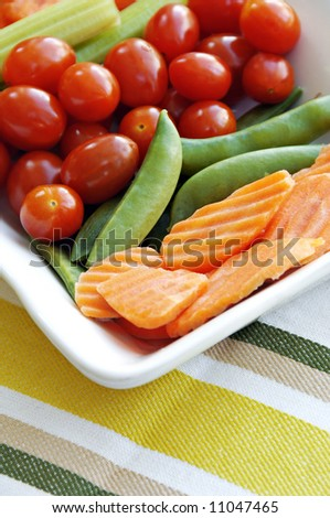 Raw vegetables to eat with dip including carrots, sugar snap peas, tomatoes, and celery sticks. - stock photo