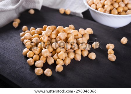 Raw wet gold chickpeas on wooden board, healthy vegan food with a lot protein, macro shot, selective focus - stock photo