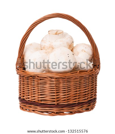 Raw white champignons in the wicker basket isolated on white background - stock photo