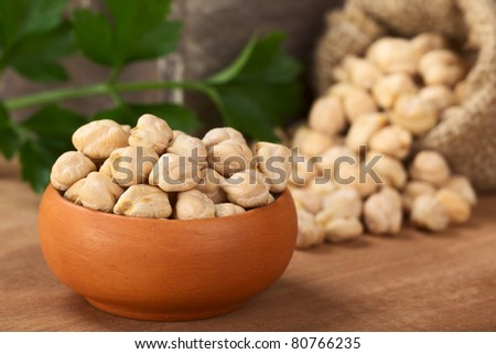 Raw white dried chickpeas (lat. Cicer arietinum) in small bowl on wood with a parsley leaf and a sack with chickpeas in the back (Selective Focus, Focus on the front of the chickpeas) - stock photo