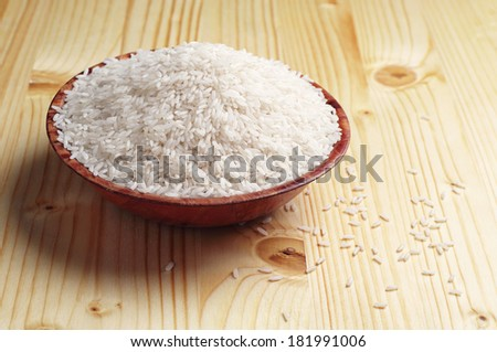 Raw white rice in bowl on yellow wooden table