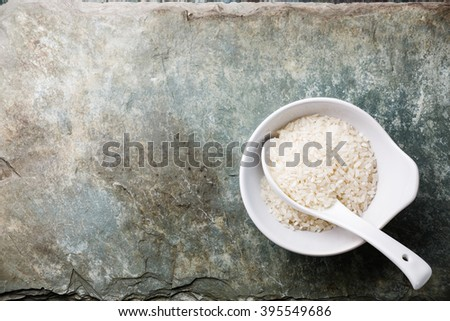 Raw white rice on gray stone slate background - stock photo