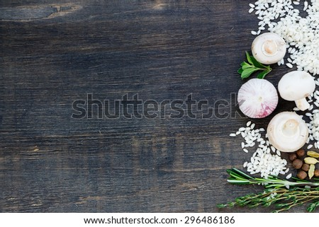 Raw white rice with ingredients for risotto on dark wooden background with space for text. Vegetarian food, health or cooking concept. - stock photo