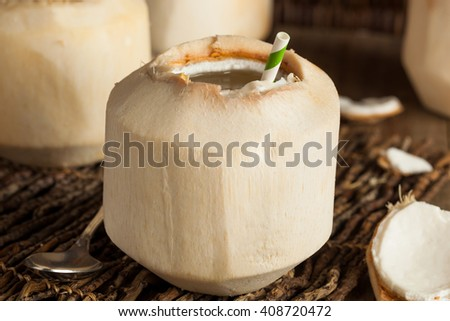 Raw White Young Coconut Drink with a Straw - stock photo