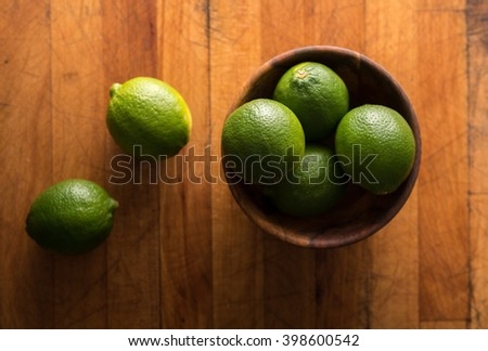 Raw whole limes in bowl on rustic wood - stock photo