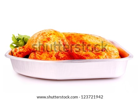 Raw whole red marinated chicken in aluminum foil tray closeup - stock photo