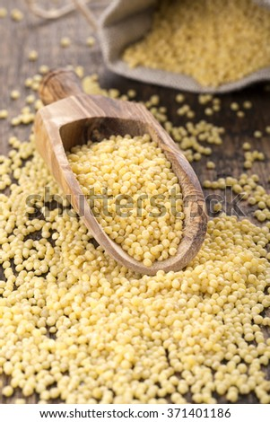 Raw yellow millet groats in the wooden scoop